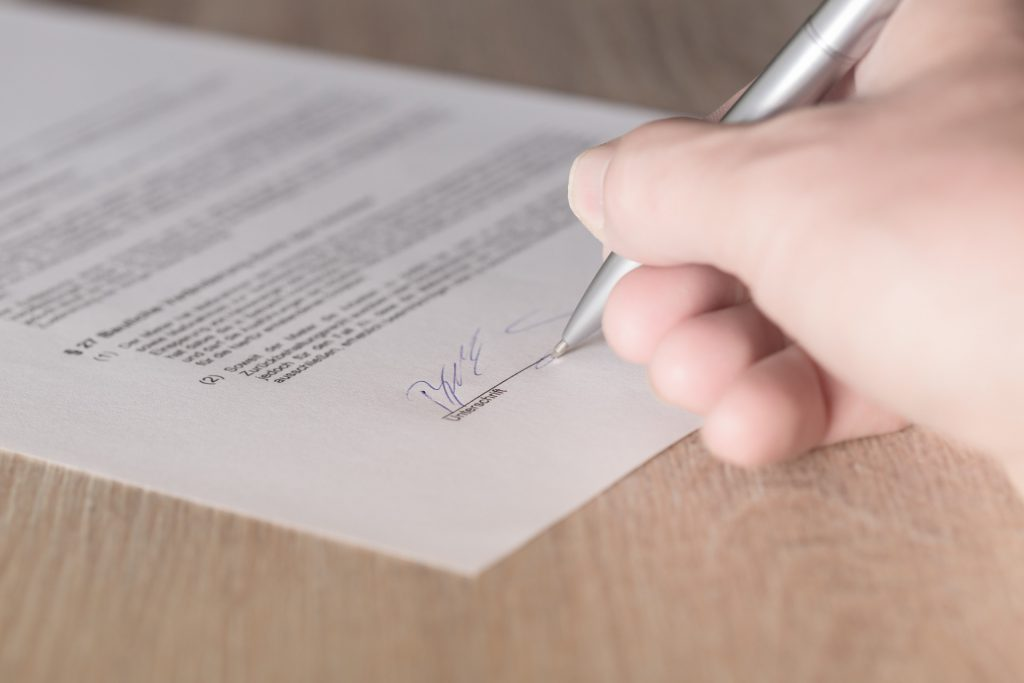 A close-up view of a hand signing a contract