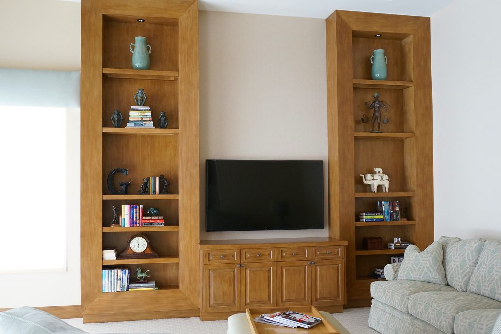 A custom entertainment center featuring standard-height cabinets with raised-panel doors in the center of the unit, and massive, ceiling-height cabinets with shelves on both ends of the unit
