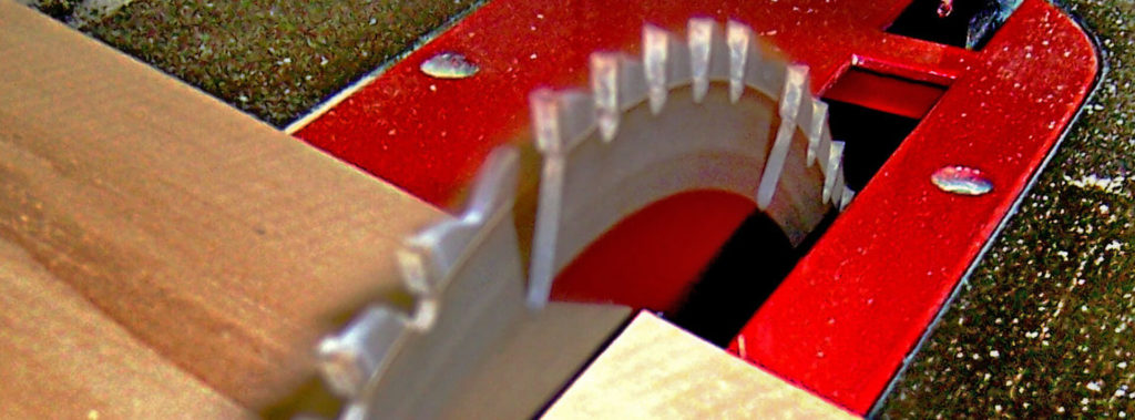 Extreme close-up of a table saw blade cutting through a piece of lumber