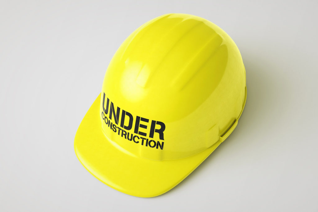 A yellow hard hat with under construction written across the front