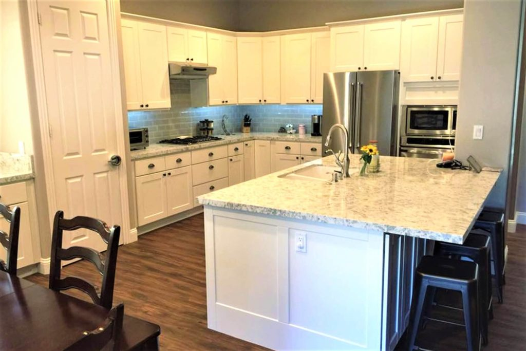 A view of a beautiful kitchen after cabinet refacing, featuring white cabinets with shaker-style doors