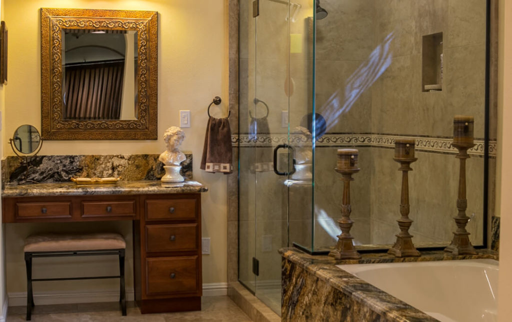 An elegant bathroom with glass shower surround and contrasting colored tile and stone