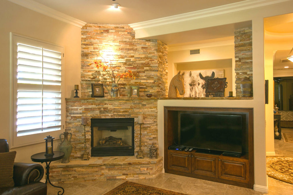 View of a modern living room with crown molding, stone fireplace, and built-in tv niche