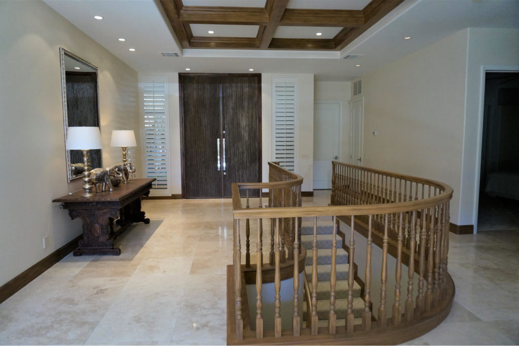 This foyer includes several beautiful examples of professional finish carpentry, including a curved stairway railing, boxed beam ceiling and custom entry doors