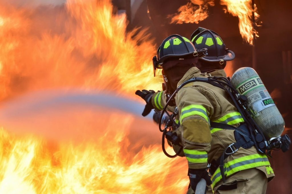 Photo of a pair of firemen as they aim their firehose at a wall of flames