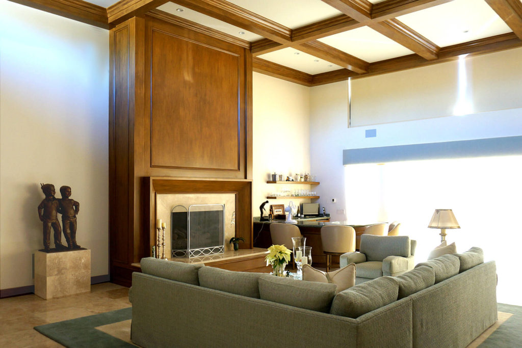 View of a tall room with boxed-beam ceiling and wood-wrapped fireplace