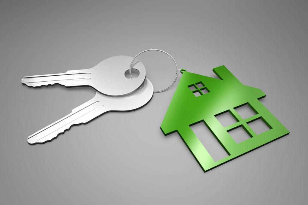 Close-up of a set of keys on a key ring with a house-shaped fob