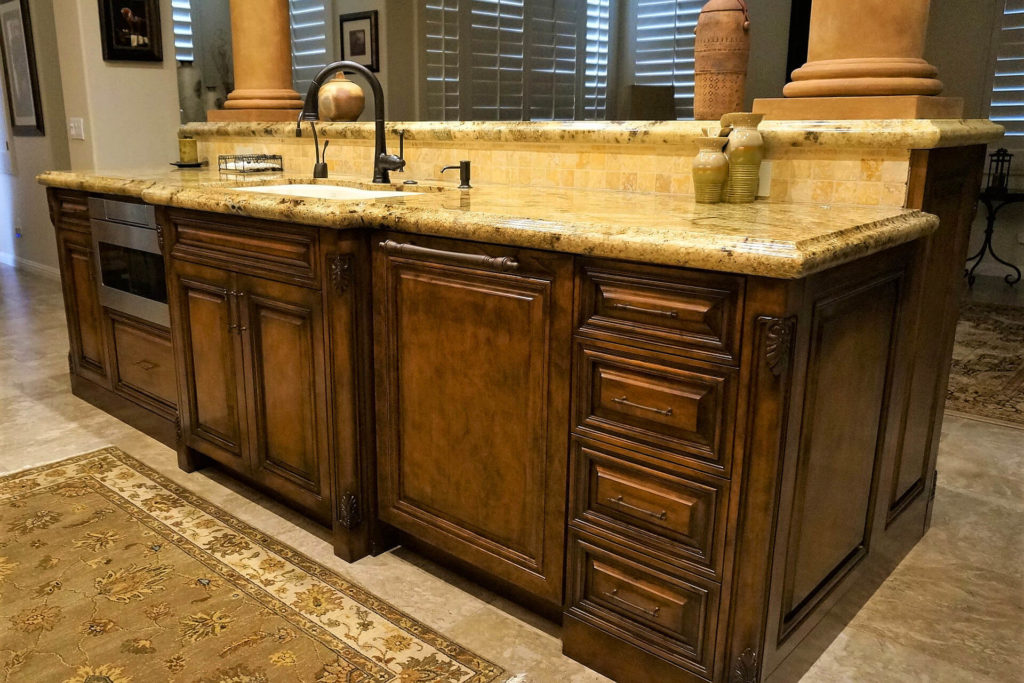 Classic-style custom kitchen cabinets, with raised-panel doors, carved-wood cornerposts, and stone countertops