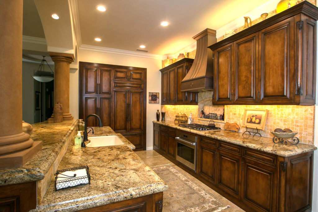 A kitchen remodel done in traditional style, with stone countertops, tile backsplash and raised panel cabinet doors