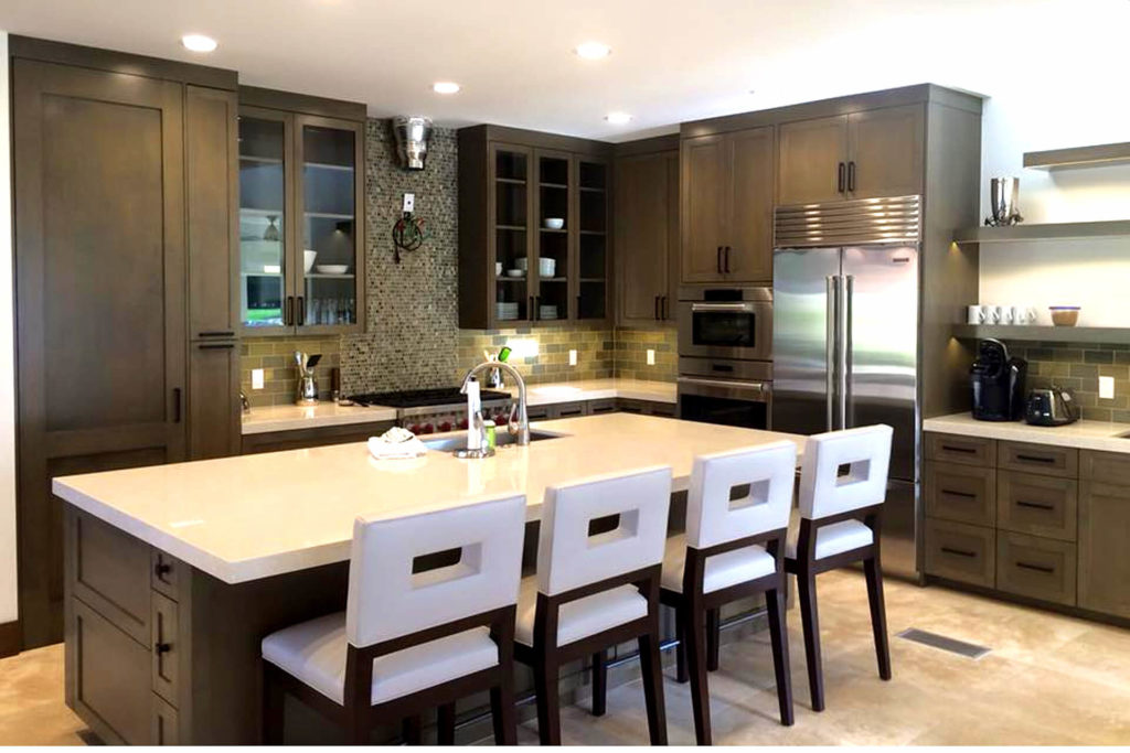 Beautiful contemporary kitchen remodel with white countertops, dark finish cabinets with shaker style doors, and a large central island