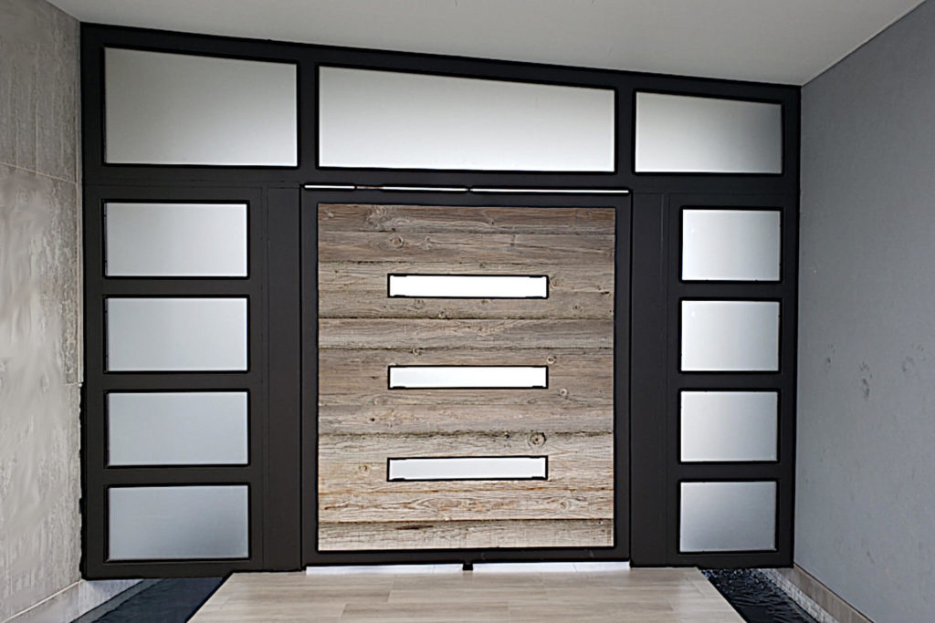 A contemporary style entry with contrasting colored wood and frosted glass panels